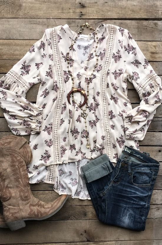 Our Living With The Blues Top is a long sleeve tunic top with floral print and v-cut neckline. Has ballon sleeves that cinch at the wrist. Lace detail down the front and back of top as well as sleeves. High/low style.