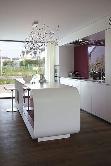 Un îlot design avec des rangements intégrés pour cette cuisine tout
