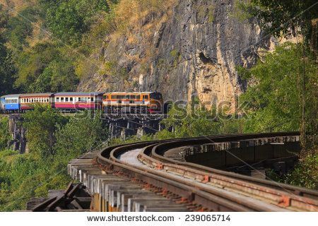 trains running on death railways crossing kwai river in kanchanaburi border of thailand-myanmar important landmark and destination to visiting and world war II history builted by soldier prisoner  - stock photo
