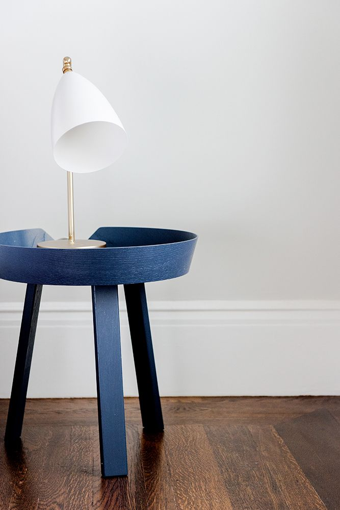 blue accent table adds color to natural wood floors and white walls