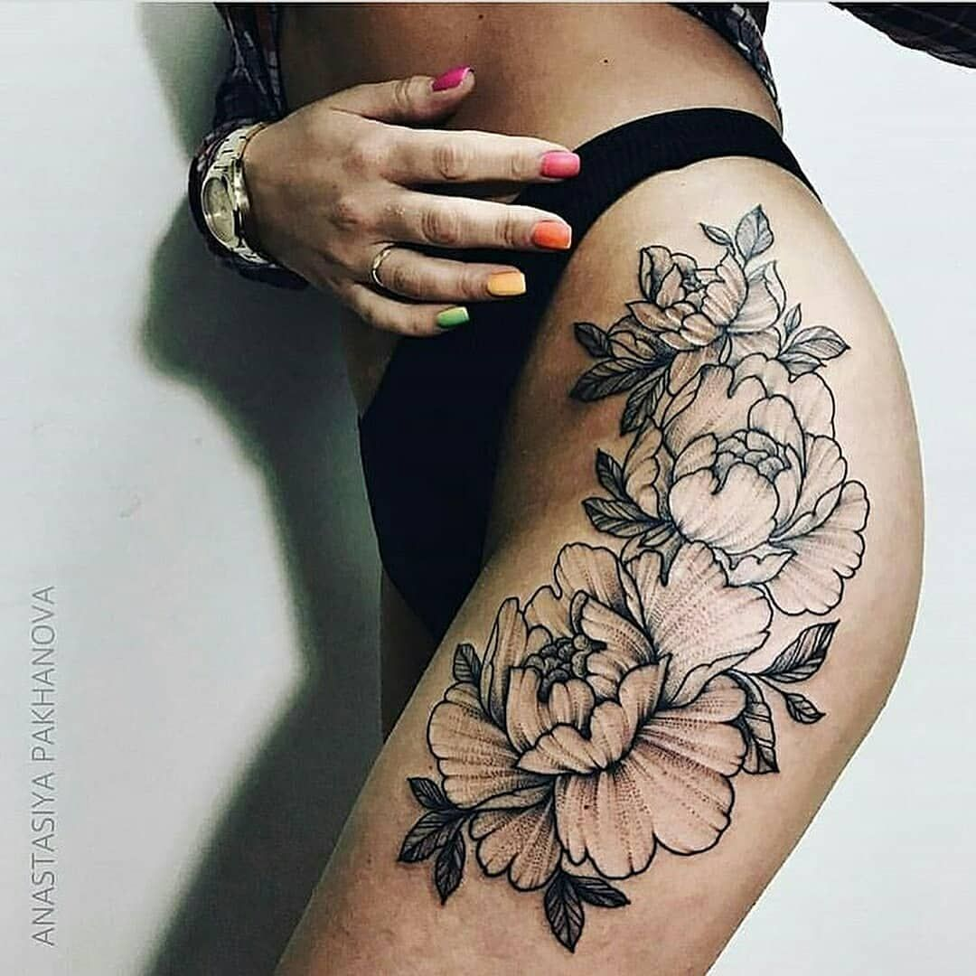 outline black flower tattoo on the left hip and