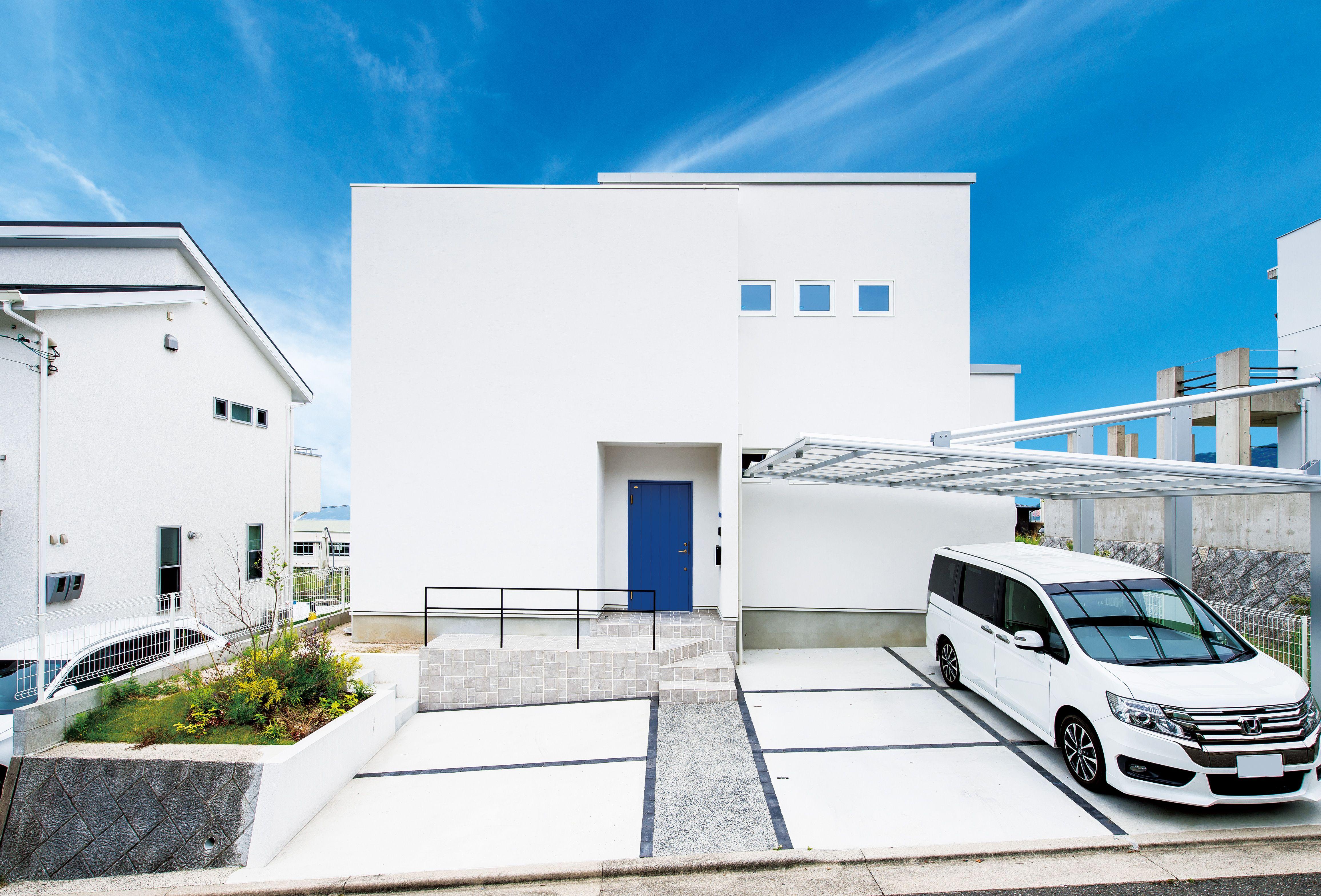 白い塗り壁に木製ドアをブルーに塗装したお家 窓枠はホワイトにする
