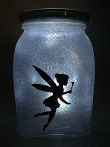 Fairy in a Jar - Tinkerbell  Made to look like you have your very own fairy in the jar. Makes the perfect night light for any room. No flame candles so its safe for use in childs room.  Fairy is made from vinyl & is stuck to the inside of the jar. (2 sided) The outside of the jar is sprayed with diamond glitter paint. Comes with a battery operated tea light in your choice of amber or clear.  Jar may vary in size or shape depending on availability.  Only use battery operated tea light…