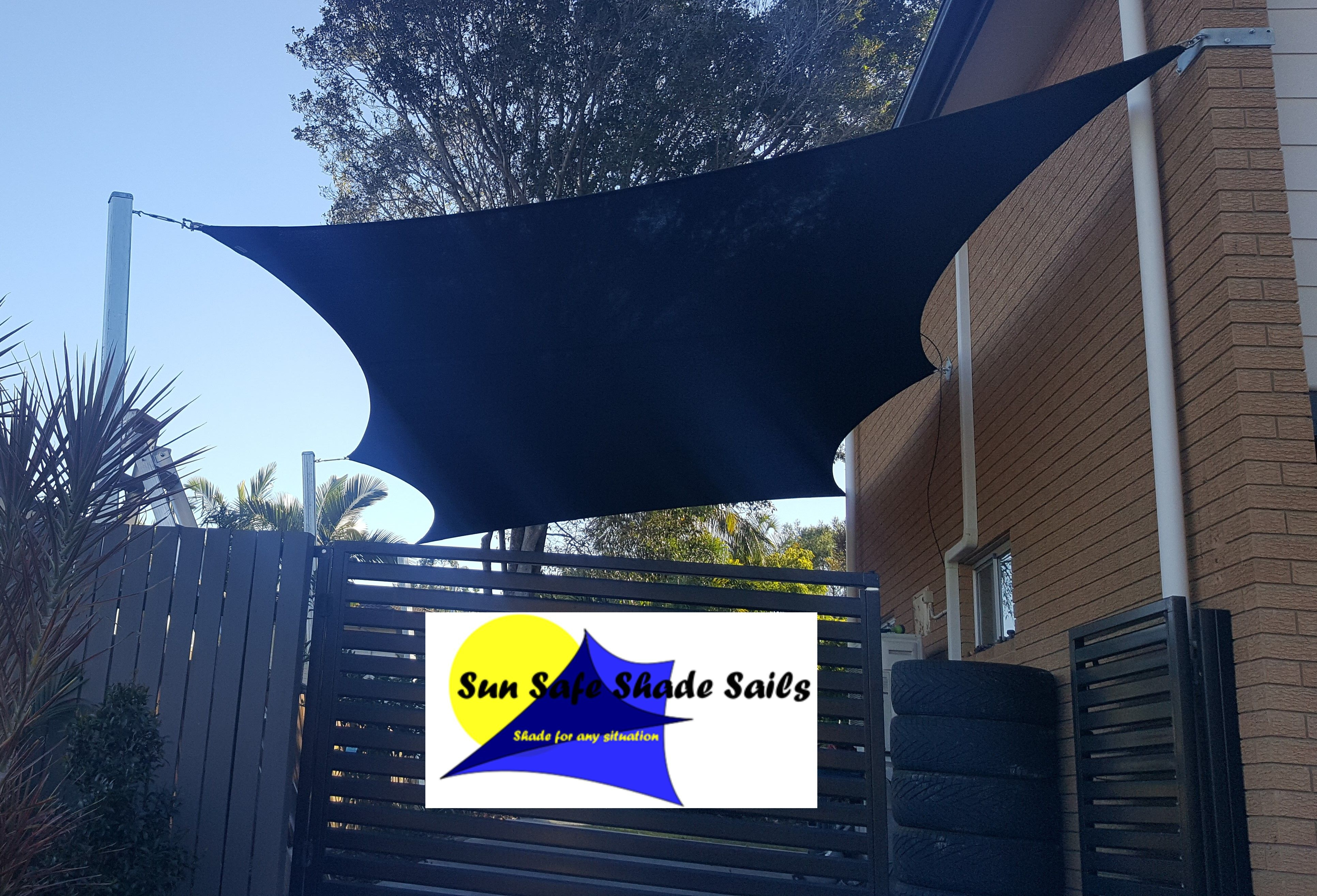 Voile D Ombrage 6 X 4 black 6 point shade sail attached to the side of the house