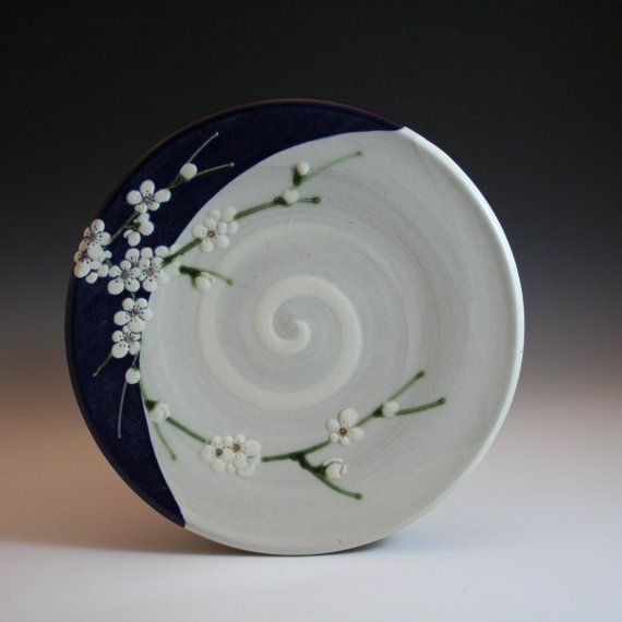 handmade stoneware plate with white plum blossoms and blue accent in an Asian/Chinese style