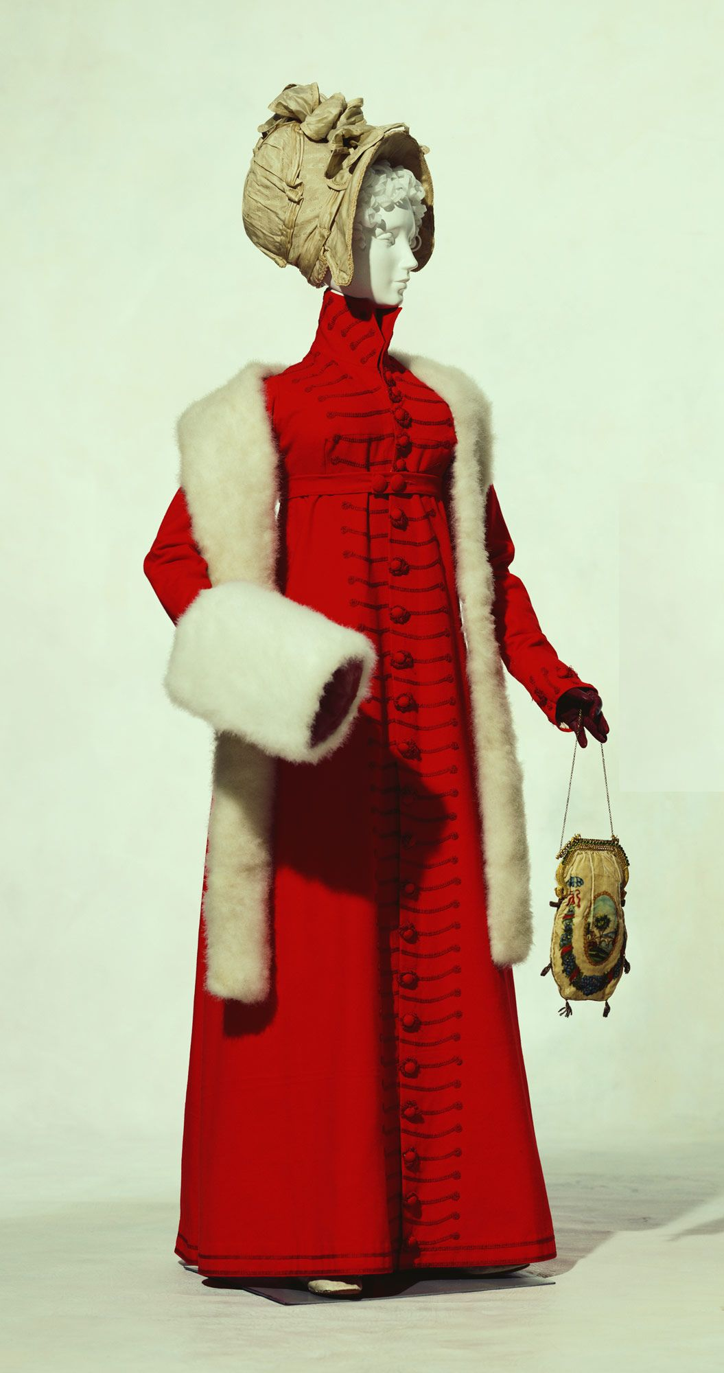 """Redingotec. 1810-England  Material:   Red wool flannel """"redingote"""" with braid and wrapped buttons in Brandenburg style; bag of beige velvet, hand-painted with floral and scenic motif, chain strap; muff and palatine of swans-down."""