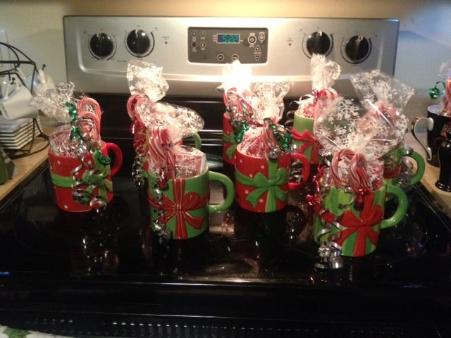 Easy, cheap, and fun gifts for coworkers. Christmas mugs filled with hot chocolate mix and candy canes with pretty ribbon. :-)