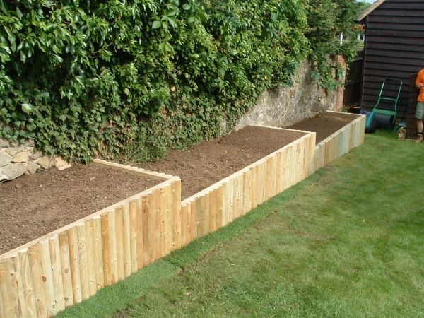 Heath raised beds wooden frame faced with wooden round for Garden decking borders