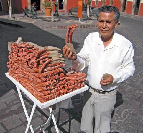 Usted puede encontrar los vendedores ambulantes para comprar cosas ricas de la. Este hombre es la venta de churros de las fresas, una fresa con sabor a donuts mexicano. La masa sale de una bolsa de pastelería, fritos y luego arrojado en azúcar ya veces canela. Las bolsas de rosquillas eran 10 pesos cada uno.