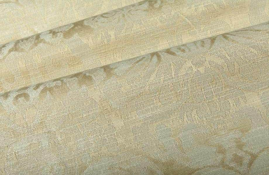 Add a classical element to the blue and white collection with this cream fabric. Dignified Upholstery Fabric in Cream has a subtle scroll pattern that has a marbled ivory and cream colorway that has a slight sheen perfect for traditional interiors.