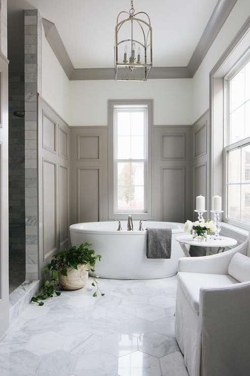 An Arch Top Lantern illuminates an elegant white and gray master bathroom equipped with an oval freestanding bathtub placed on large marble hex floor tiles beneath a window partially framed by dark gray wainscoting.