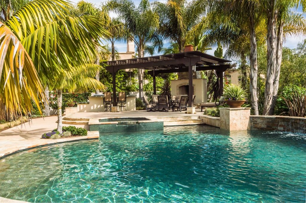 a outdoor kitchen with natural stone pavers and a roof extension outdoor kitchen and pool