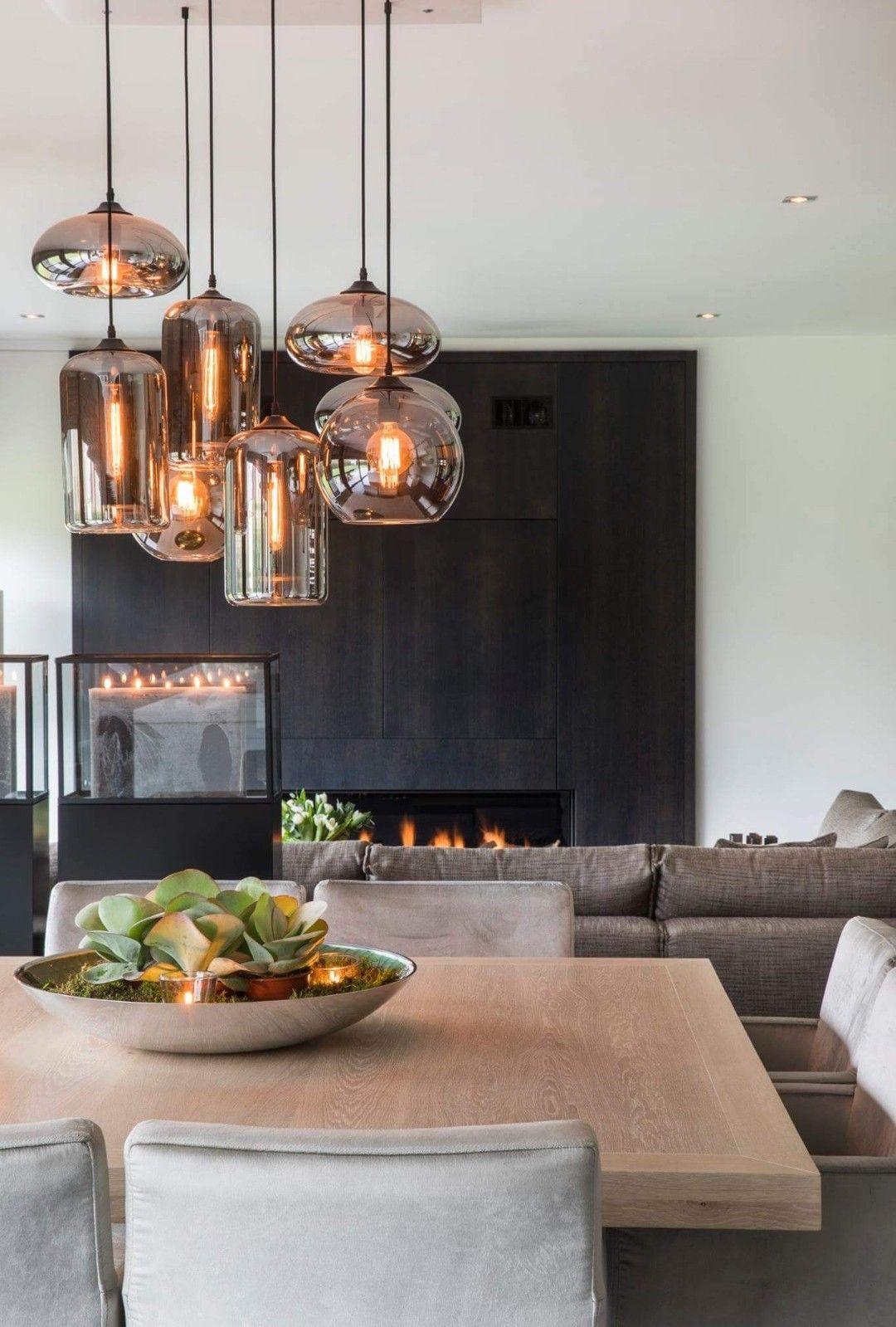 Metallized glass made pendant lamps illustrating a beautiful straight black flat fireplace facing giant sofa #pendantlighting