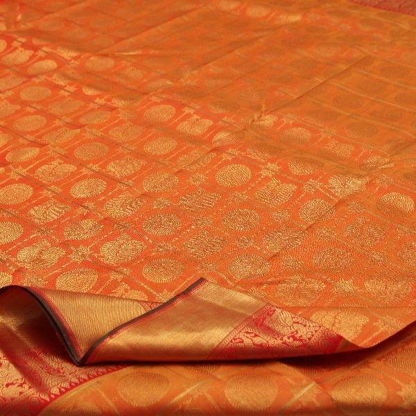 Orange #silk is smothered with gold checks, with peacock and chakram motifs caged in each square. The gold border is crowned with a smear of kumkum red, woven with yali and peacock motifs. The fiery red pallu boasts of gold peacock and temple motifs giving this sari a touch of the ornate and auspicious. A plain red blouse with the running border completes the look of this handwoven #Kanjivaram sari. View Kanjivarams in this shade at Sarangi. Code 650126847.