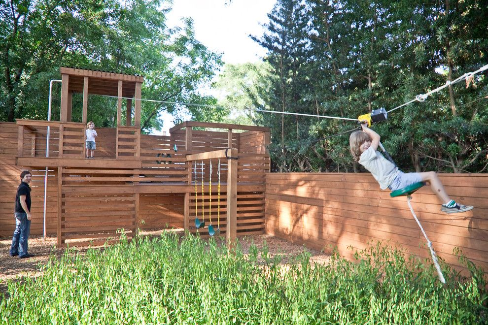 splashy backyard playground equipment in landscape traditional with hog wire fencing next to treehouse alongside build