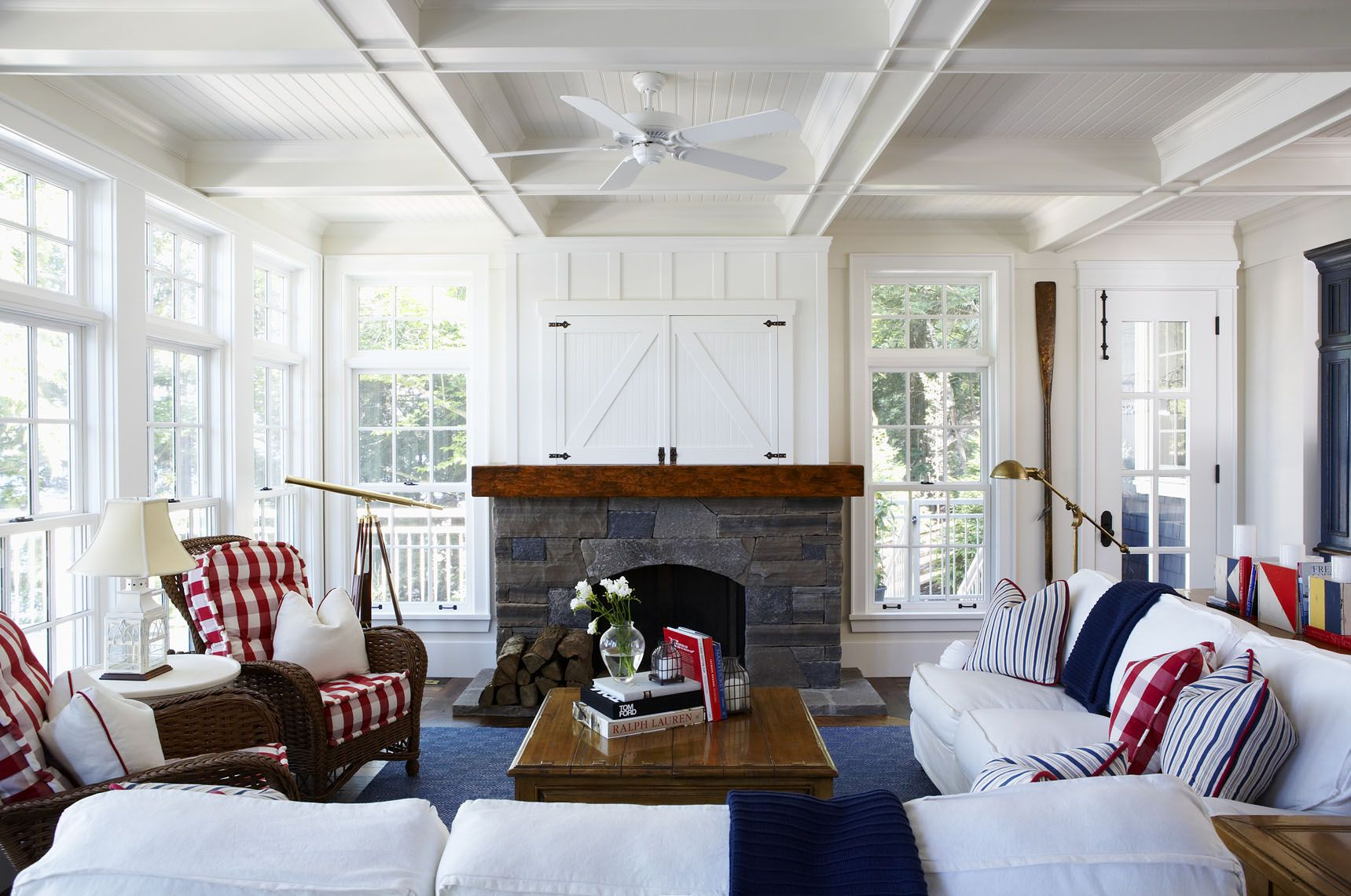 white slipcovered sofas with dark wicker chairs; red and blue ...