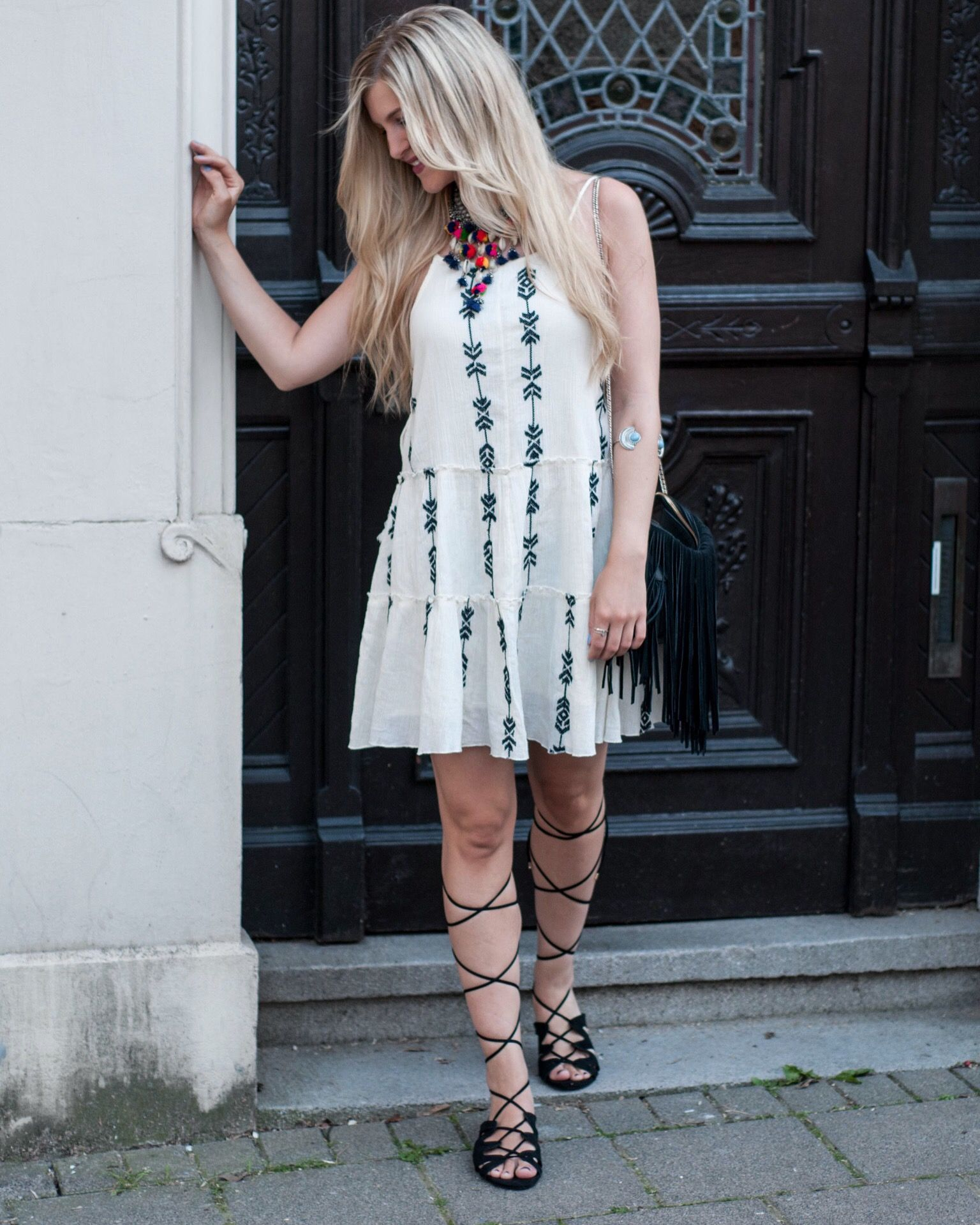 Boho vibes in the city with this ethno dress, lace-up sandals and tassel necklace.