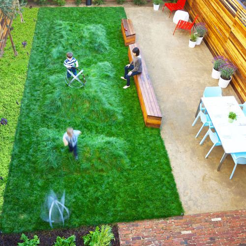 Landscape design, grass, bumps for kids to run up and down, outdoor dining, wood stained fence.