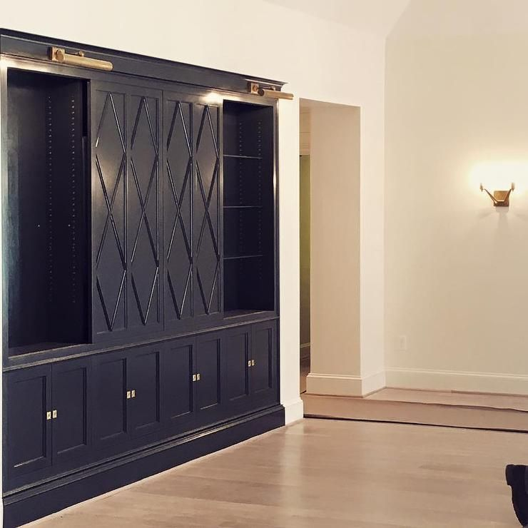 Chic Living Room Features Navy Blue Built In Cabinets Fitted With Diamond Pattern Sliding Doors