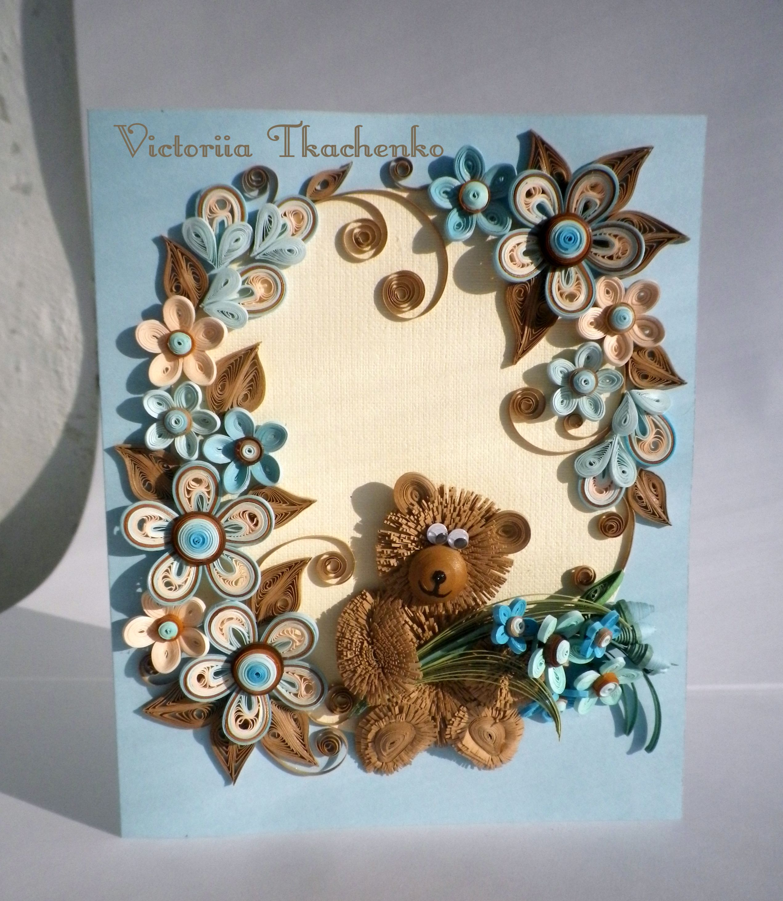 Greeting card made in quilling technique with cute bear ornate with folowers in blue and brown colors.