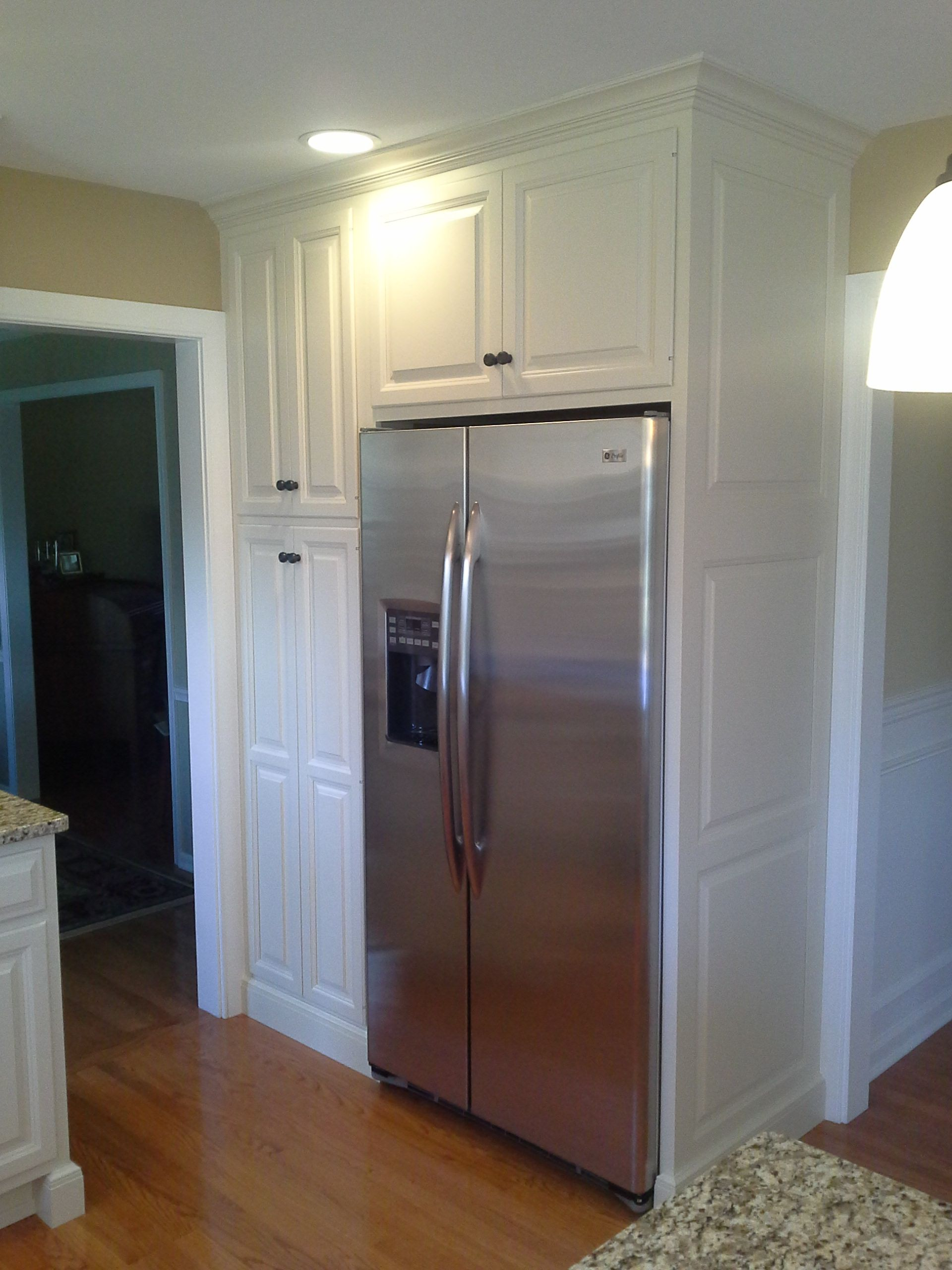 Close Up Of Stainless Steel Refrigerator And White Painted Pantry Cabinet With Wainscot