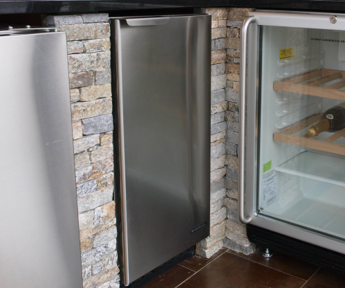 A Stainless Steel Ice Maker Is Concealed Behind A Cabinet Door Of A Gray Blue Ki Kitchen Countertops Pictures Affordable Kitchen Countertops Kitchen Renovation