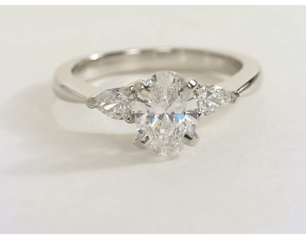 e092870cce534 Oval shaped diamond nestled in between two pear shapes set in a ...
