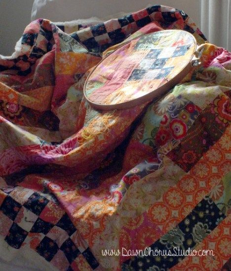 Brightly coloured lap quilt being hand quilted draped over a chair. © Stephanie Boon, 2015 www.DawnChorusStudio.com