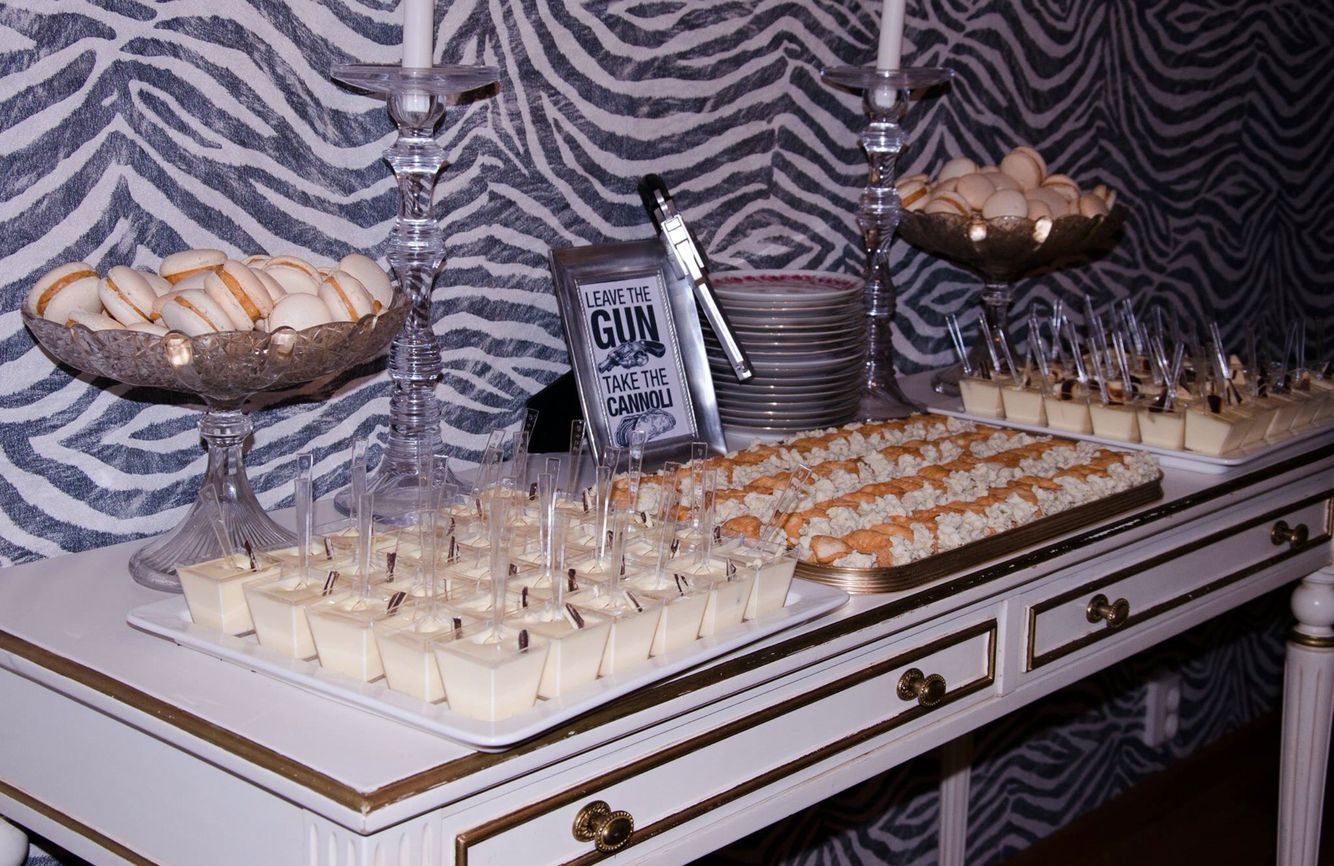 """Even the food should be a part of your theme. This dessert table served mini cannolis with a sign featuring a quote from the movie. """"Leave the gun, take the cannolis"""""""
