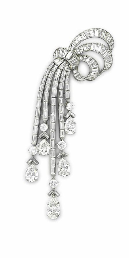 A DIAMOND BROOCH, BY VAN CLEEF & ARPELS: Designed as a gathered tapered baguette-cut diamond ribbon, to the pear-shaped, circular and baguette-cut diamond articulated cascade, circa 1950, 4 3/8 ins., mounted in platinum. Signed Van Cleef & Arpels (partially obscured), N.Y., no. 15733. Via Christie's.