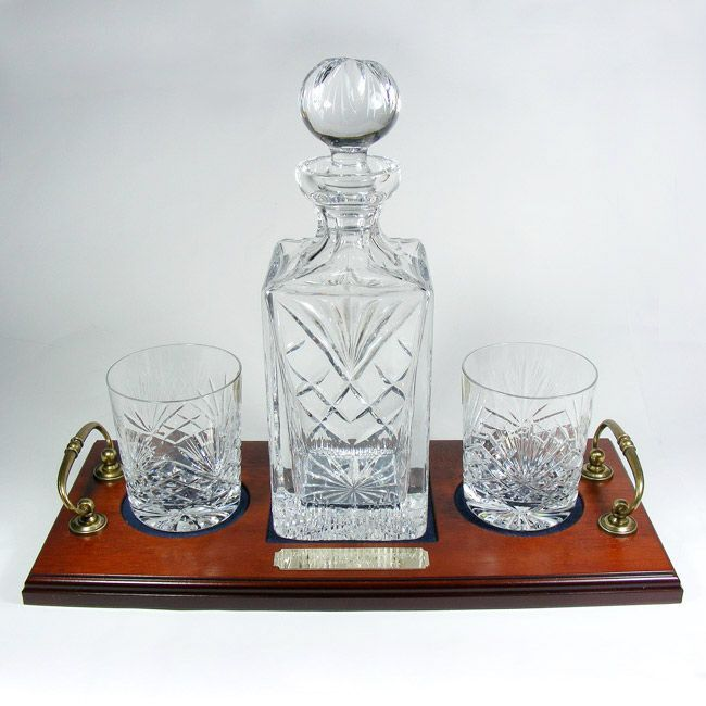 A high quality 24 Fully Cut Lead Crystal Decanter and two 8oz whisky tumblers presented on a wood veneer tray with brass handles Large plaque on the
