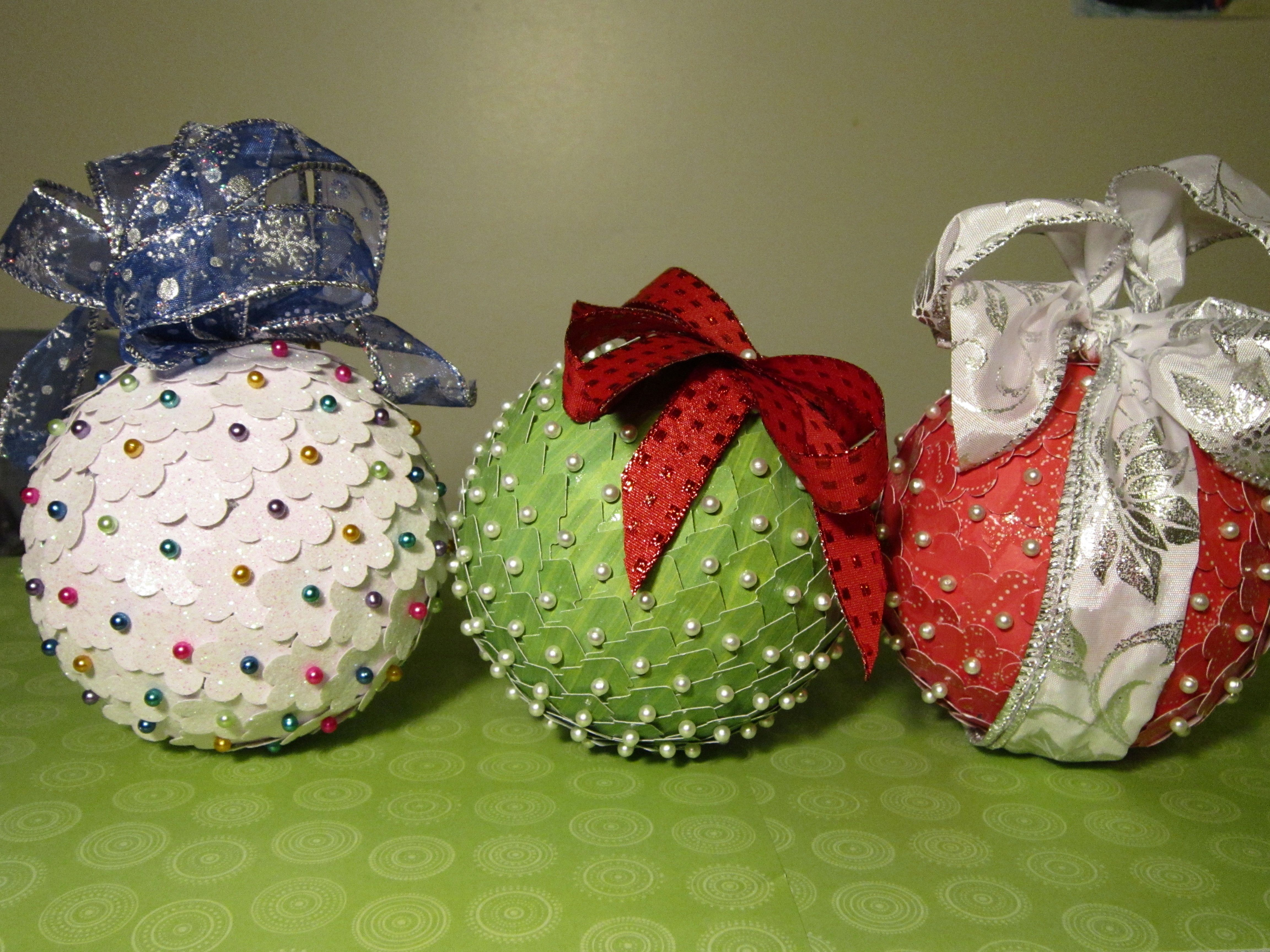 Homemade Christmas ornaments made from styrofoam balls, quilting pins, and  punched out cardstock.