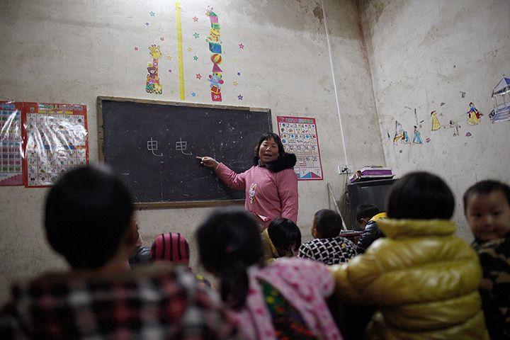 A teacher teaches children Chinese characters during a class