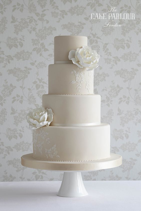 'REGENCY ROSE' Wedding Cake - Whimsical white sugar roses and simple lace piping decorate this pale coffee coloured cake. More