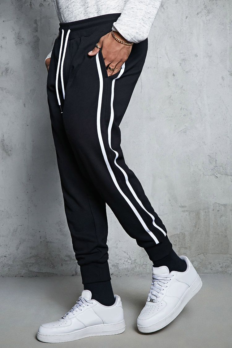 5febe823 A pair of French terry joggers featuring side stripes, on-seam pockets, an  elasticized drawstring waist, and ribbed knit ankle cuffs.