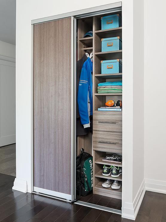 A Brown Melamine Sliding Door Opens To A Condo Foyer Closet Filled With Modular Brown Melamine S Closet Organization Custom Closet Doors Closet Storage Systems