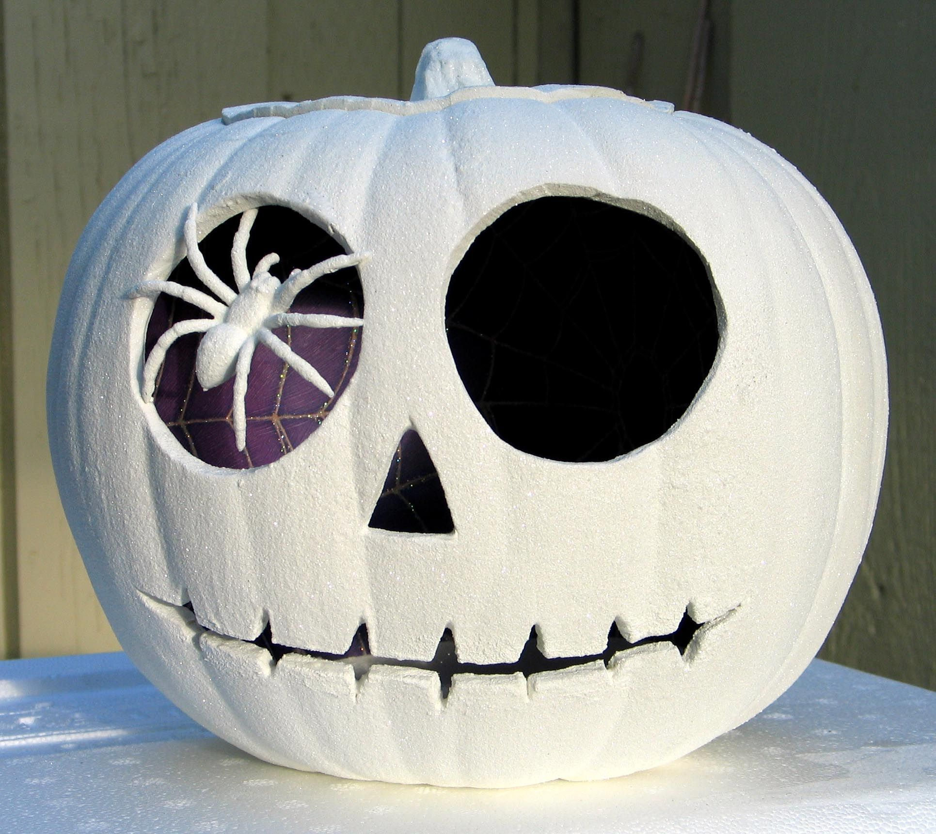 A very simple pumpkin with a craft store spider pinned into its \'eye ...