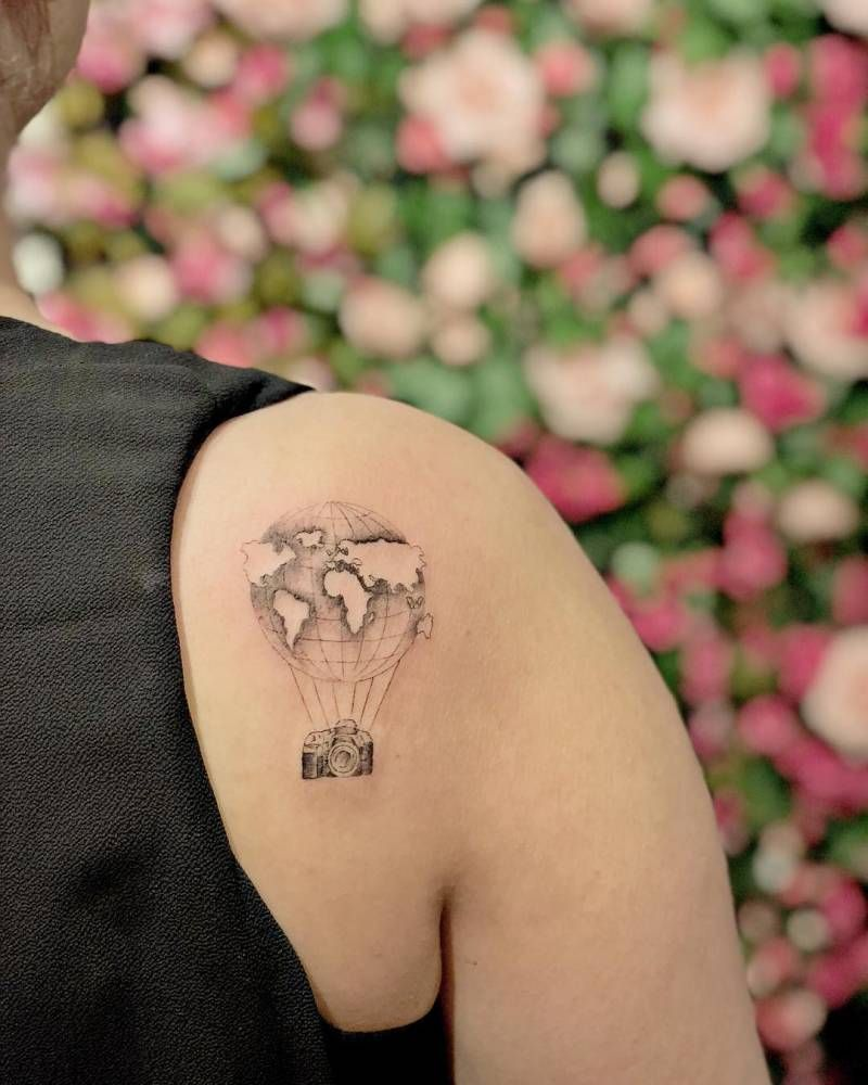 Surrealist air balloon tattoo on the right shoulder blade.