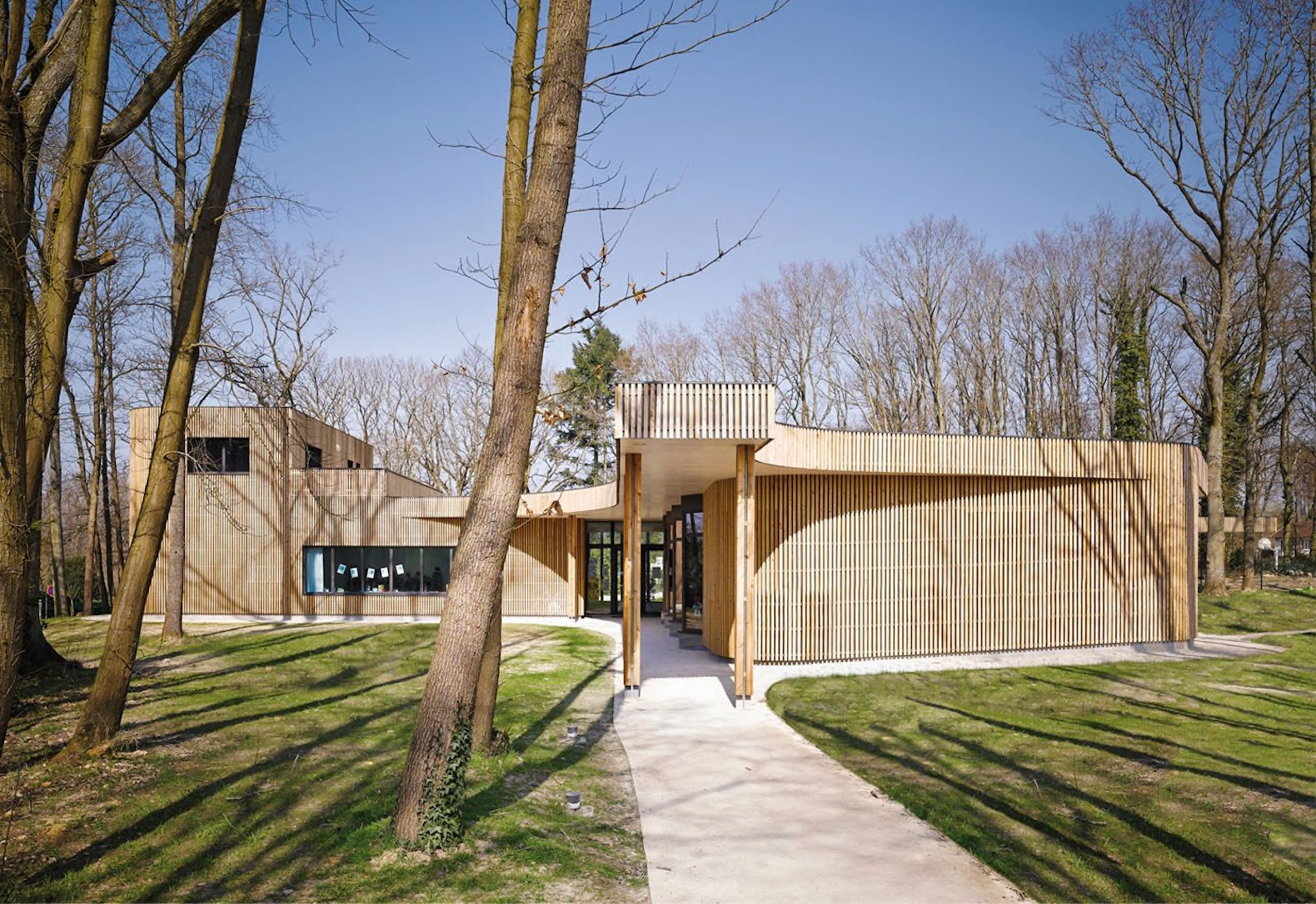 Timber Clad School Weaves Between The Trees In A French Commune. School  ArchitectureEco ArchitectureSchool DesignSustainable ...