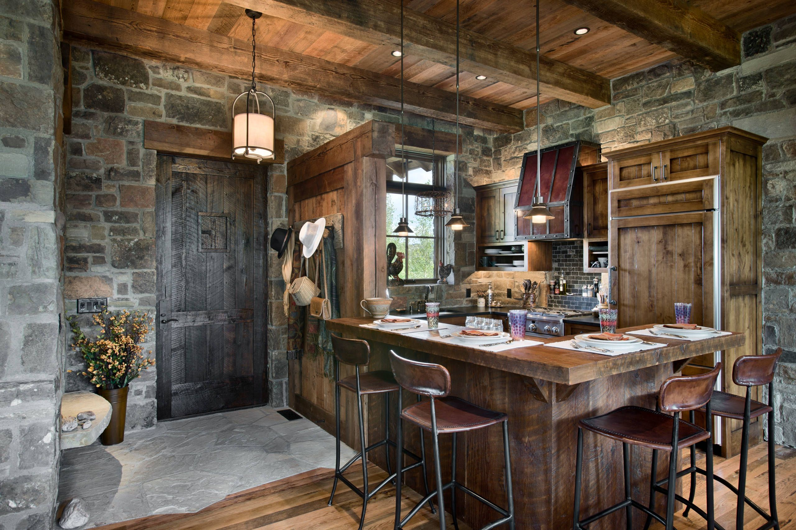 A Strong Kitchen Full Of Stone Large Wood Beams And Metal Accents Log Home Kitchens Interior Design Cabin Interiors
