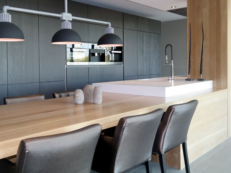 Binnenkijken interieur keuken met kookeiland en tafel in