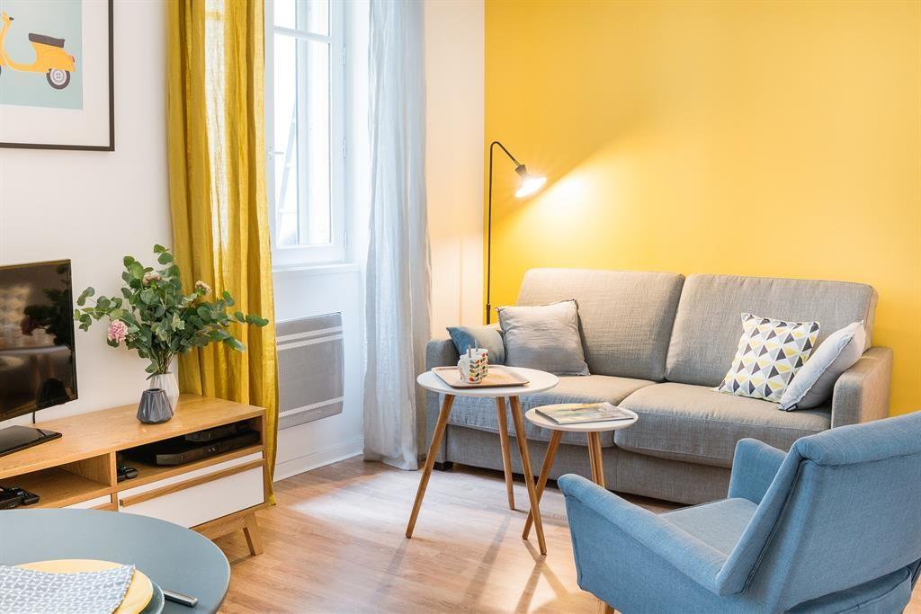 Living room with yellow wall | Salon avec un canapé avec un grand ...