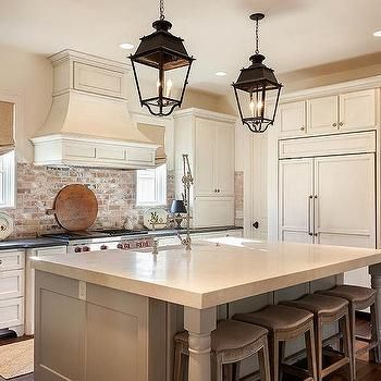 Kitchen With Used Red Brick Backsplash And Lantern Pendants With Grey Island And White Cabinets