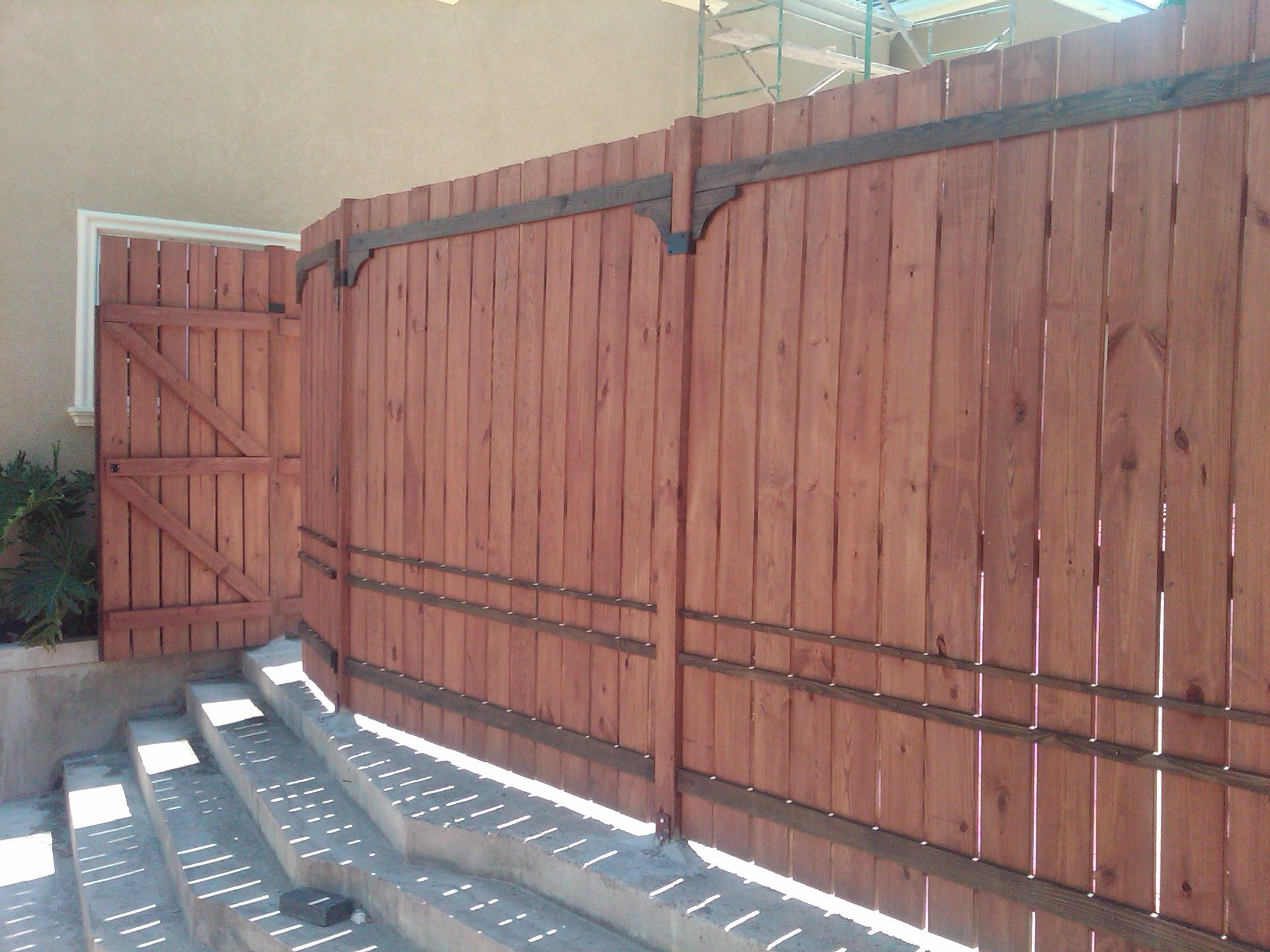 Wooden perimeter fence and entrance gate. Entrance gates