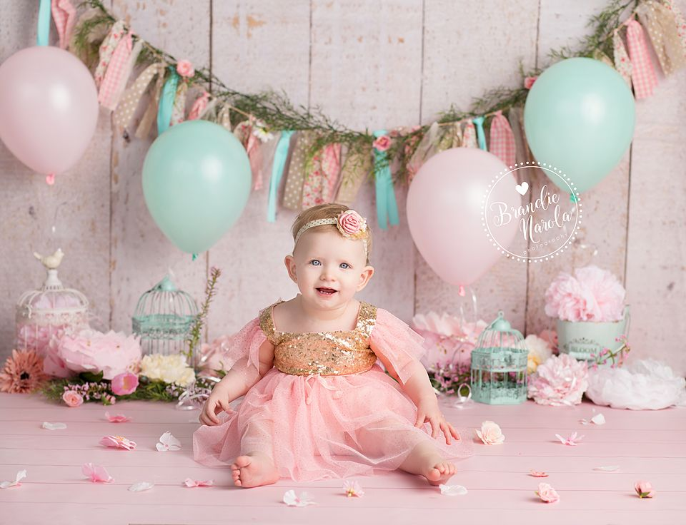 Baby in pink and gold dress in themed baby cake smash
