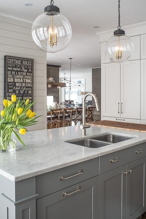 Two Regina Andrew Large Globe Pendants illuminate a gray kitchen
