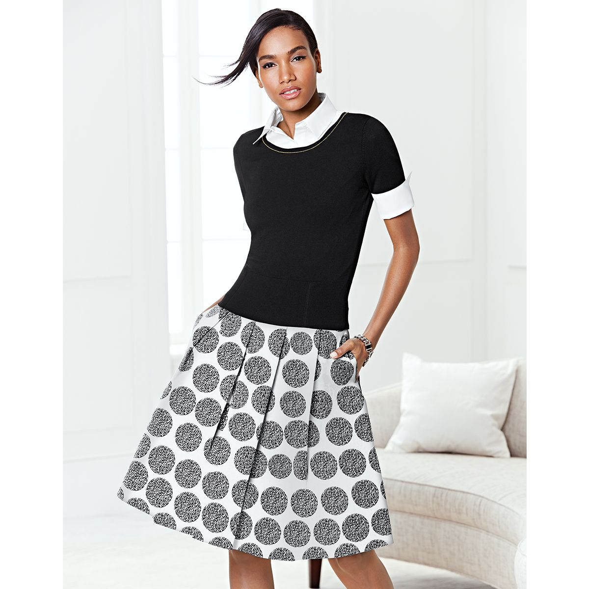 Pleated perfection flares out in classic sophistication across this faille skirt with a modest midi length and bold black and white dot print. #WHBM #WorkMastered