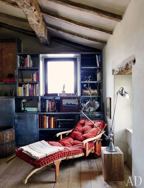 The rustic study features built-in shelves and a custom-made chaise lounge | archdigest.com