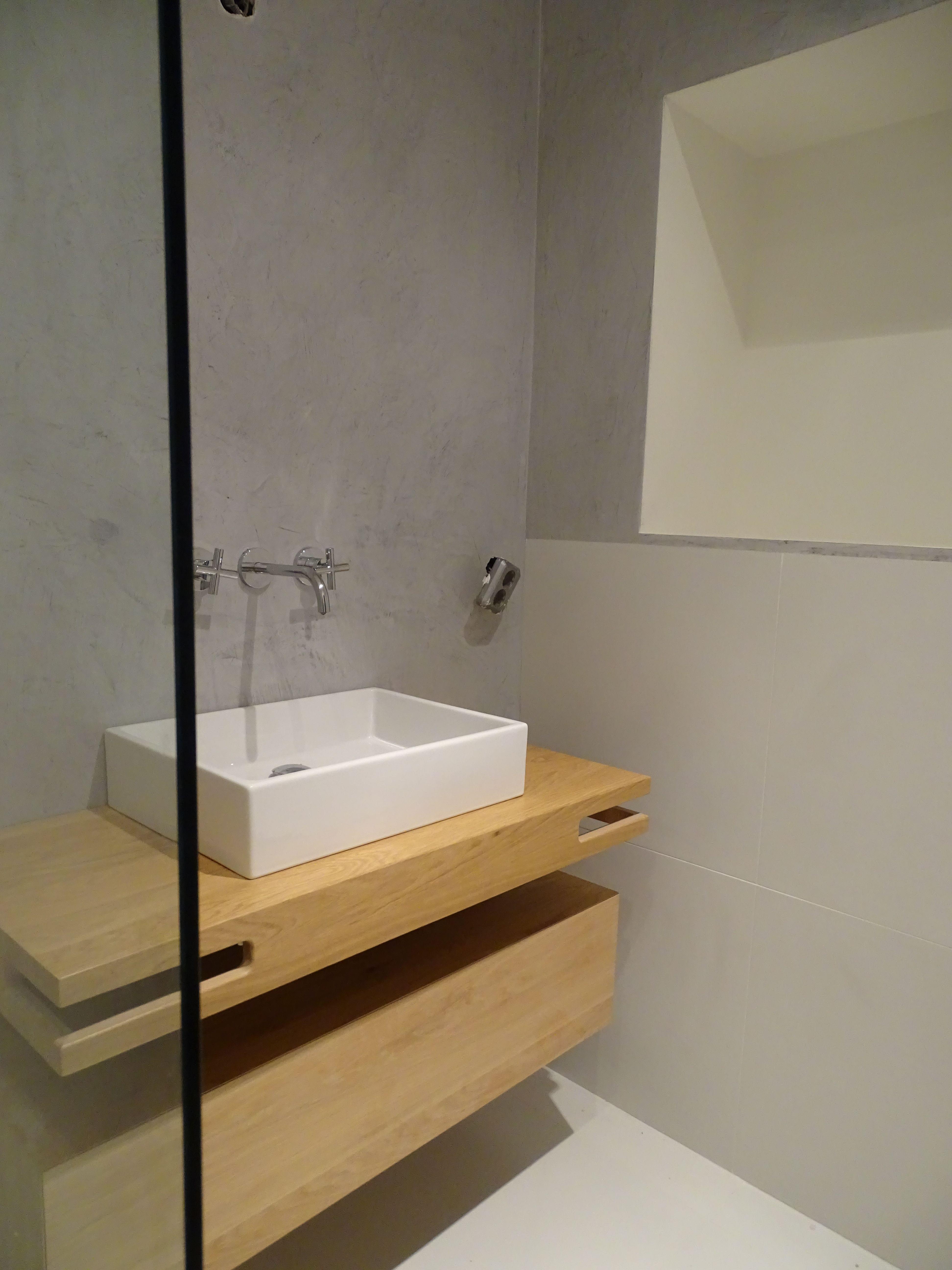uitgevoerde betonlook in een lichtgrijze kleur in een badkamer