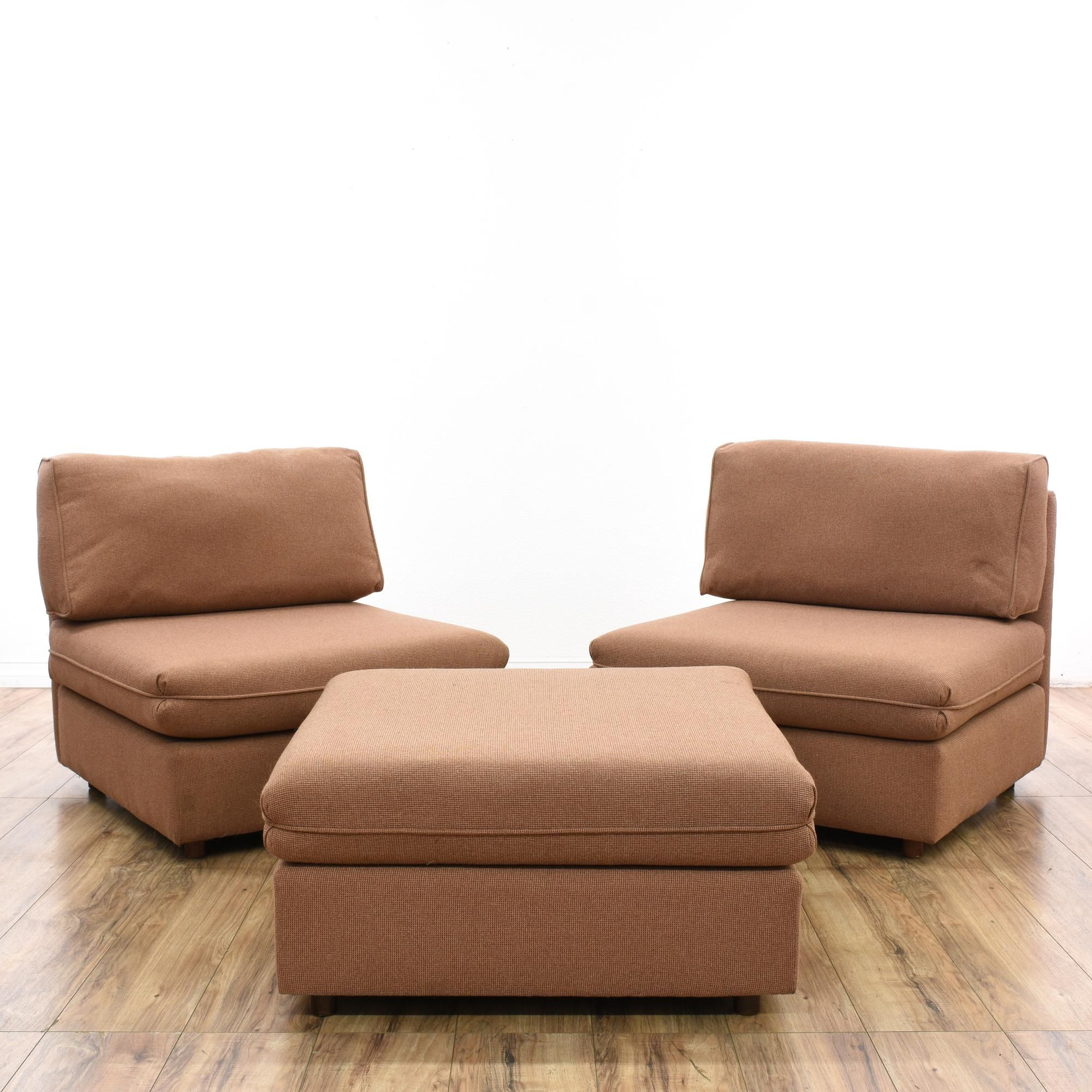 This pair of armless sofa chairs & ottoman are upholstered in a